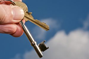 Holding new property keys against a bright blue sky.